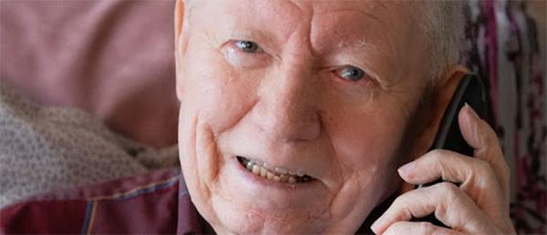 older man speaking on the phone smiling