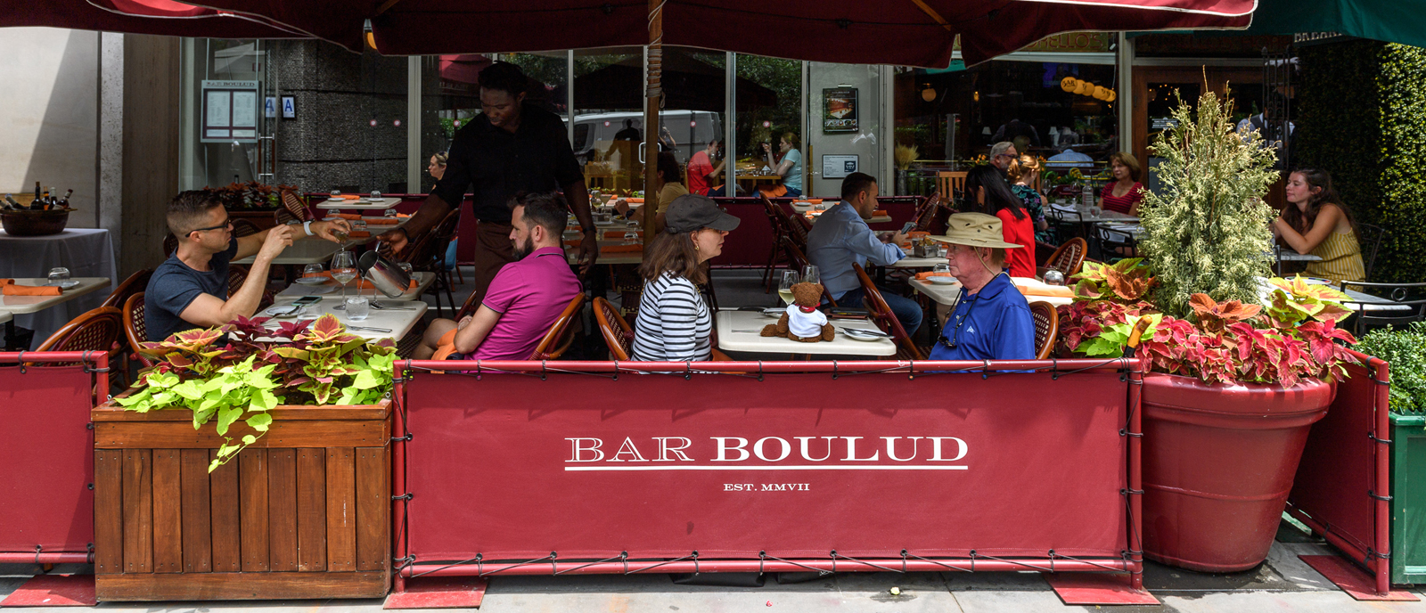 a busy sidewalk cafe in the summertime at Bar Boulud on Broadway