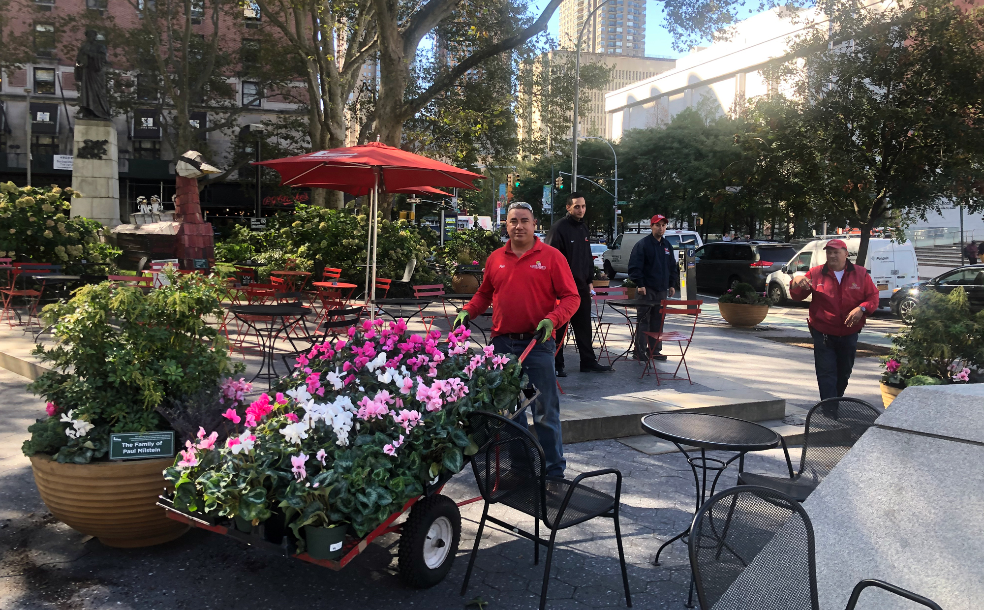 Bulfamante Landscaping worker wheels fall flowers through the park for planting
