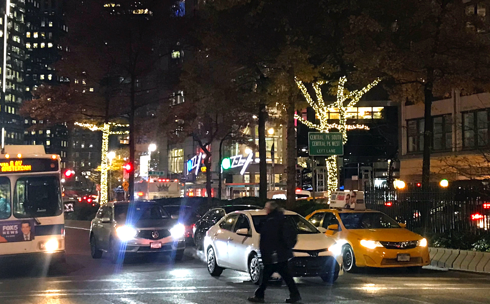 several Broadway trees light up with holiday lights between 61st and 62nd street with cars waiting at the streetlight