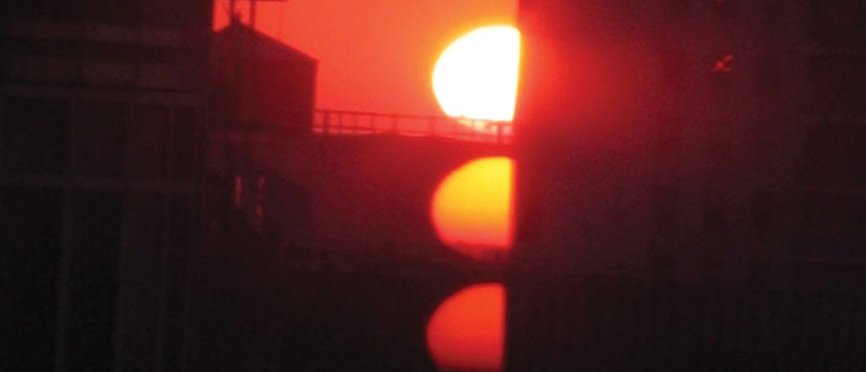 a red sun glares over some city buildings in the evening
