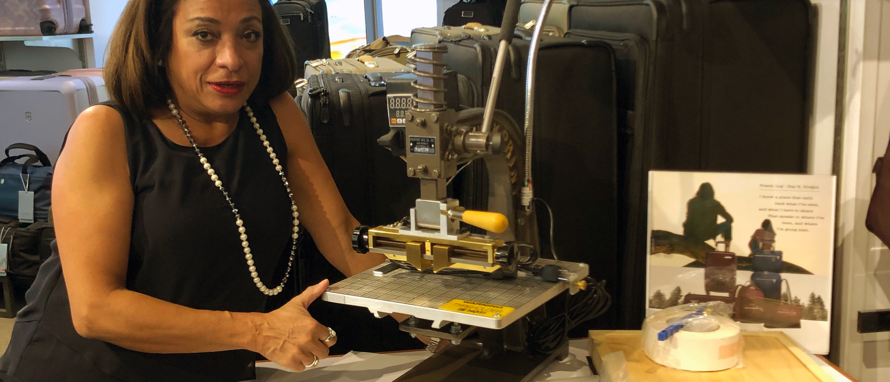 store manager at Innovation Luggage poses with engraving machine
