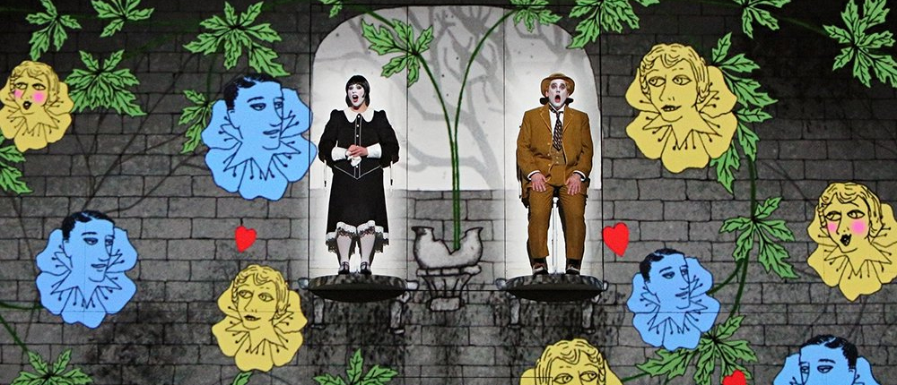 British theater group 1927 performing The Magic Flute among CGI flowers vines and cartoon faces