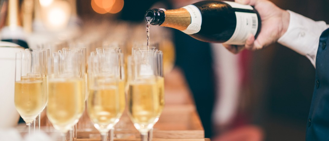 a waiter pours champagne into a row of glasses on a wooden bar top