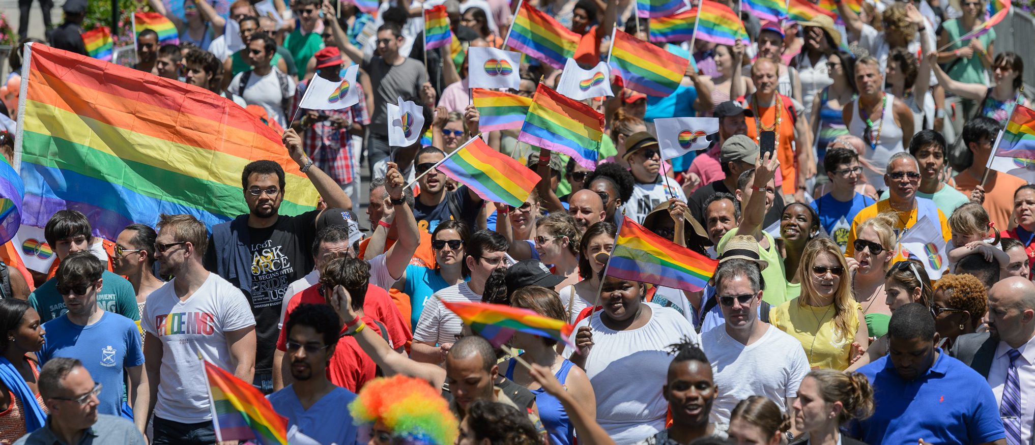 a large crowd of people march through Manhattan with rainbow flags
