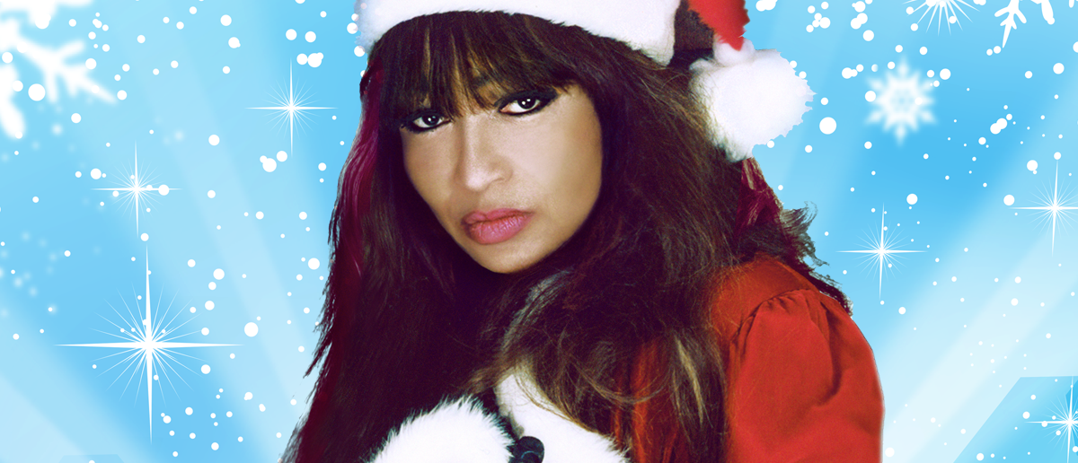head shot of Ronnie Spector in a Santa hat and matching red Santa dress