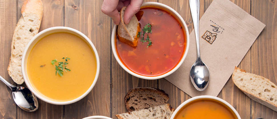 three soups on a wooden cutting board at Le Pain Quotidien with slices of bread and a hand dipping bread into one bowl
