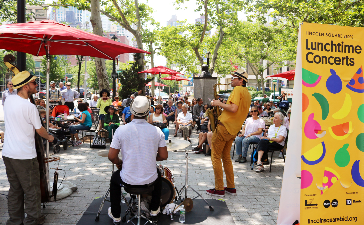 A trio band plays before a crowd at Richard Tucker Park during the 2018 Lunchtime Concert Series