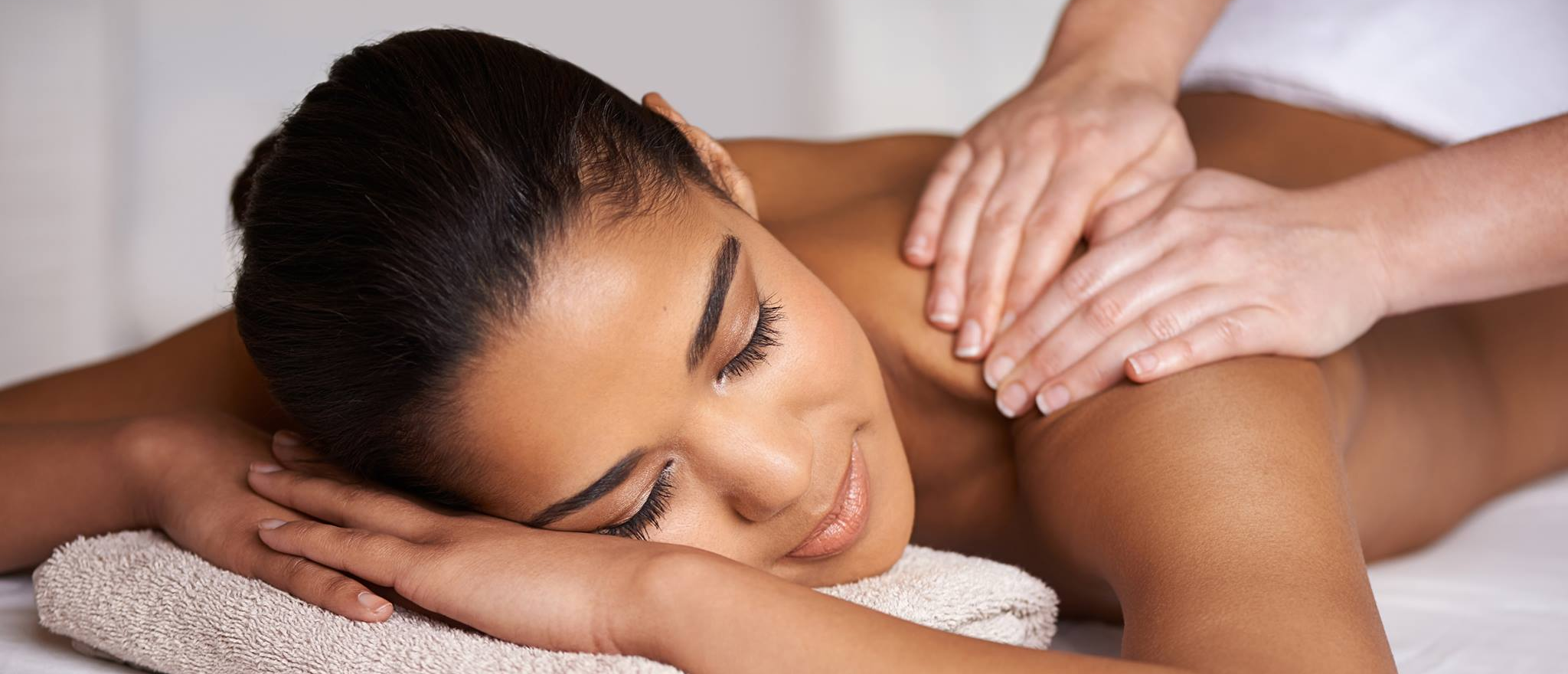 a woman receives a shoulder massage while lying down on a massage table at Upper West Spa