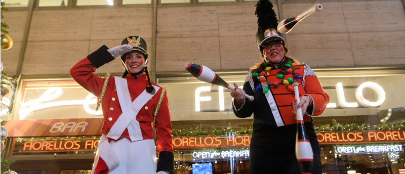 two stilt walkers dressed as soldiers pose for a photo during Winter_s Eve
