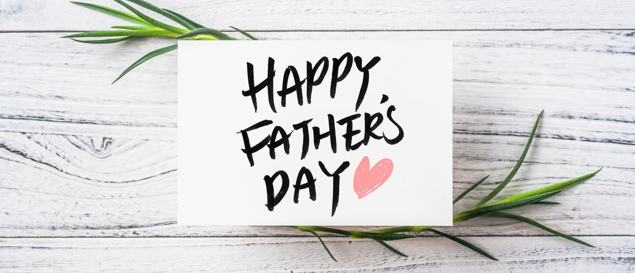 white card on a table says Happy Fathers Day with a pink heart