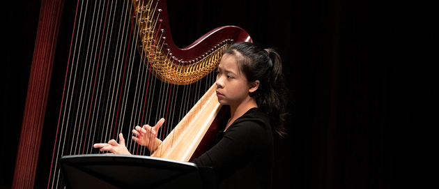 Juilliard musician plays the harp against a black background