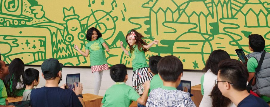 two children dance in front of a group of other children in apple branded tee shirts
