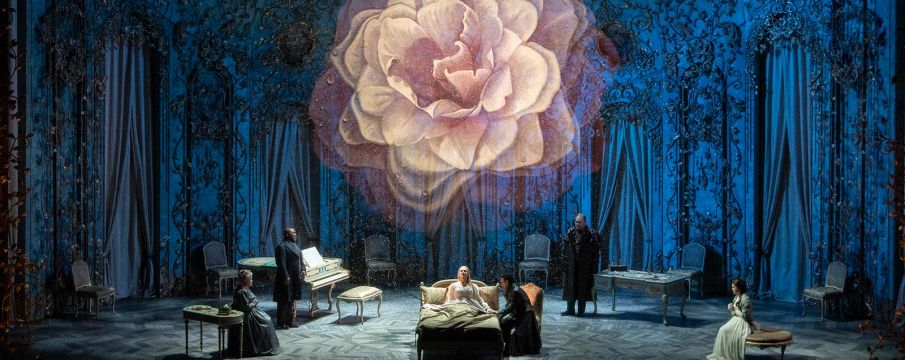 photo of the cast performing a scene from La Traviata on-stage at the Met Opera