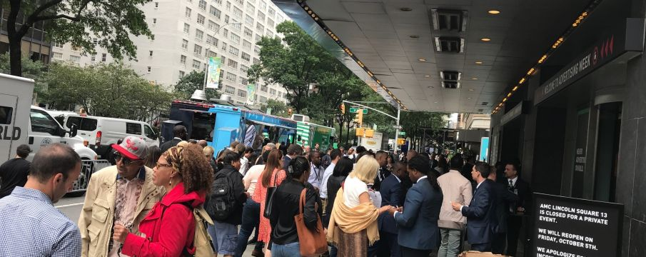 people gather in a crowd on the sidewalk in front of AMC Lincoln Center for Ad Week 2018