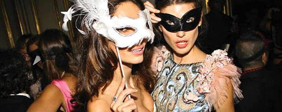 two young women wear masquerade masks at a party
