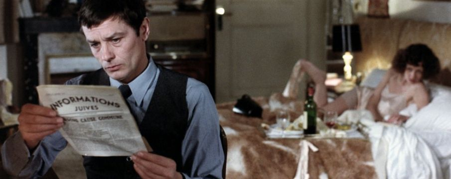 a still from Monsieur Klein--Klein reads the paper while a woman lounges in bed in the background