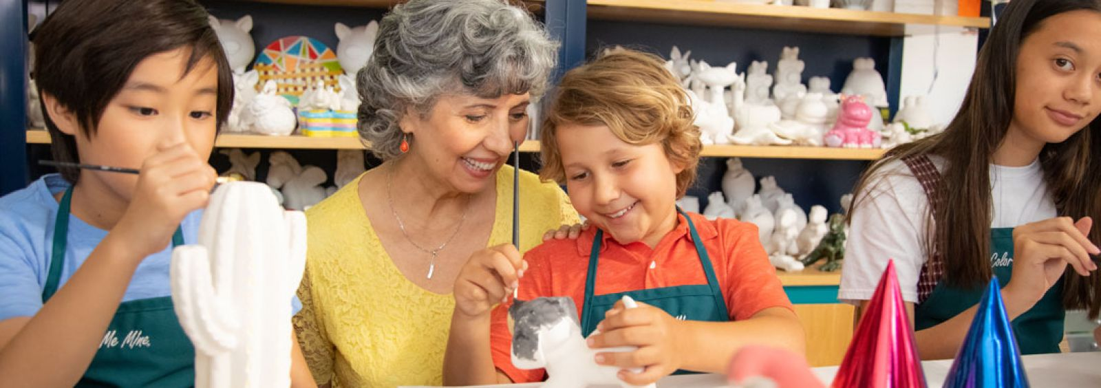 An older woman helps a young boy paint a piece of pottery at a color me mine studio