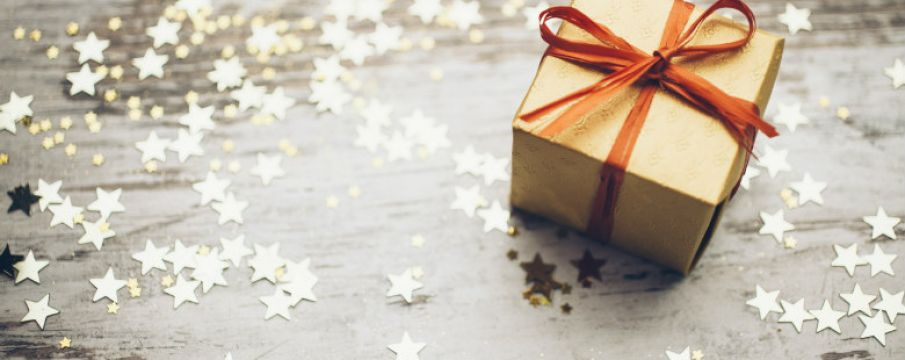 brown paper wrapped gift box with a red ribbon on a table surrounded by cutout stars