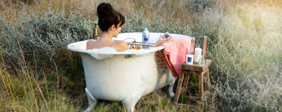 woman in a claw tub bath enjoys herself with luxury products