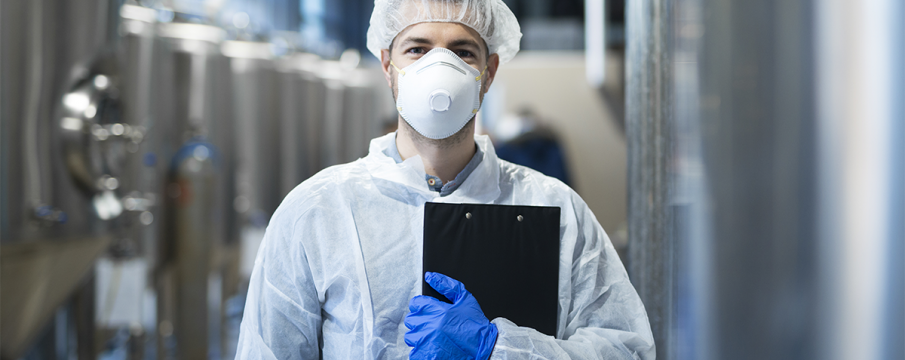 man wearing PPE mask, headcap, and gloves in a factory setting