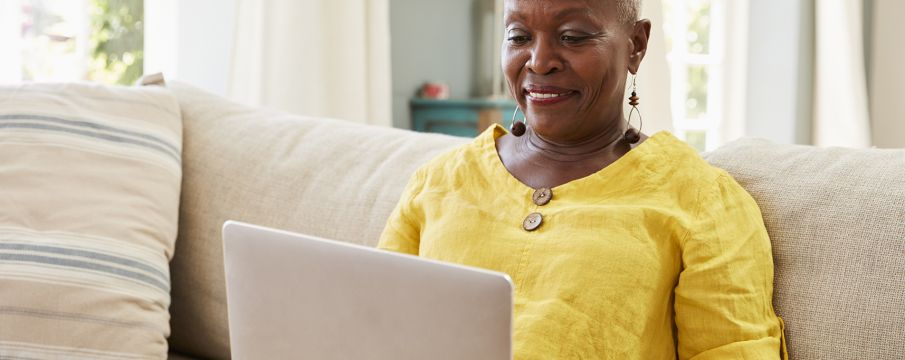 an older woman uses her laptop on her living room couch