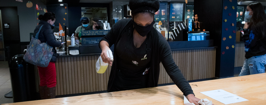a worker inside of the Starbucks at 63rd St and Broadway wipes down a counter top for patrons with disinfectant