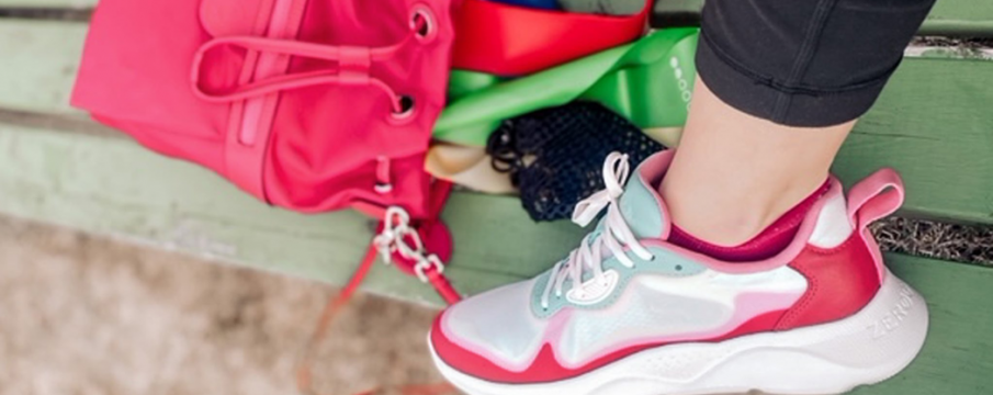 close up of a pink running sneaker on a woman's foot propped up on a bench near her backpack