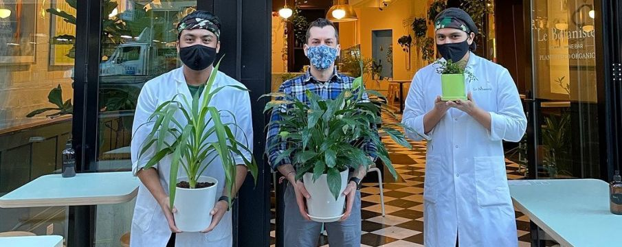 three young employees from Le Botaniste Upper West Side pose in front of the restaurant with plants