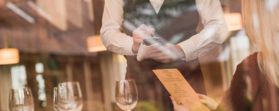 looking through the window, a waiter takes the order of a woman at a table of a nice restaurant with wine glasses on the table