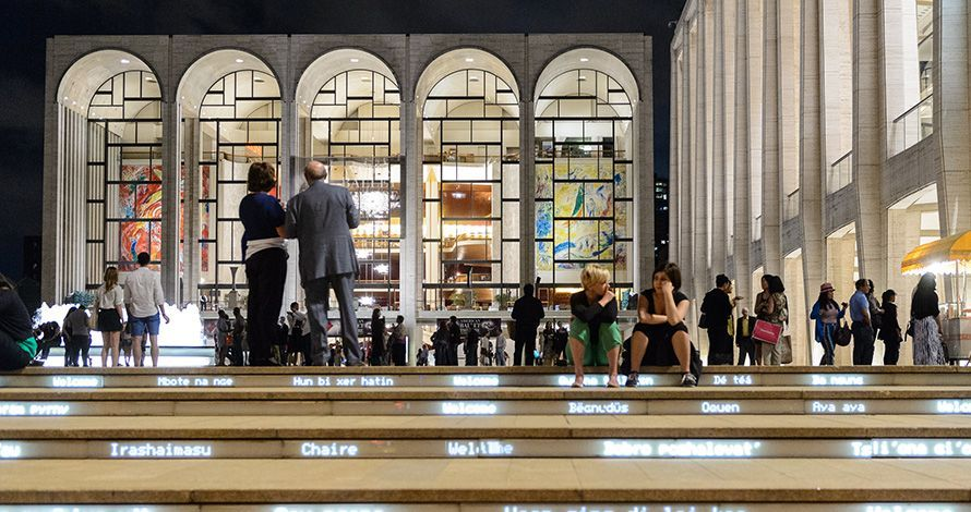 Lincoln Center's campus on a busy summer evening in view of the Metropolitan Opera